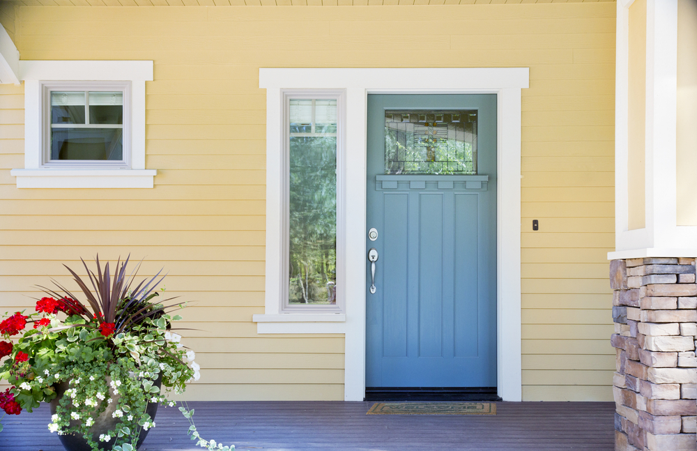 Door with beautiful yellow siding next to it